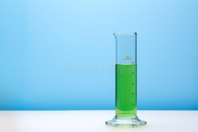 Цилиндр лаборатории градуированный с зеленой жидкостью r стоковые изображения rf