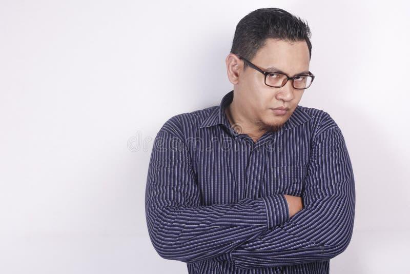 Циничный азиатский бизнесмен смотря к камере с гневом стоковые фото