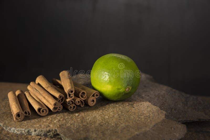 Циннамон и известка на камне и темной предпосылке стоковое фото