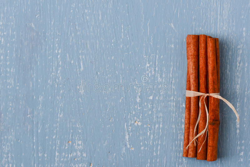 Циннамон на голубой деревянной предпосылке стоковое изображение