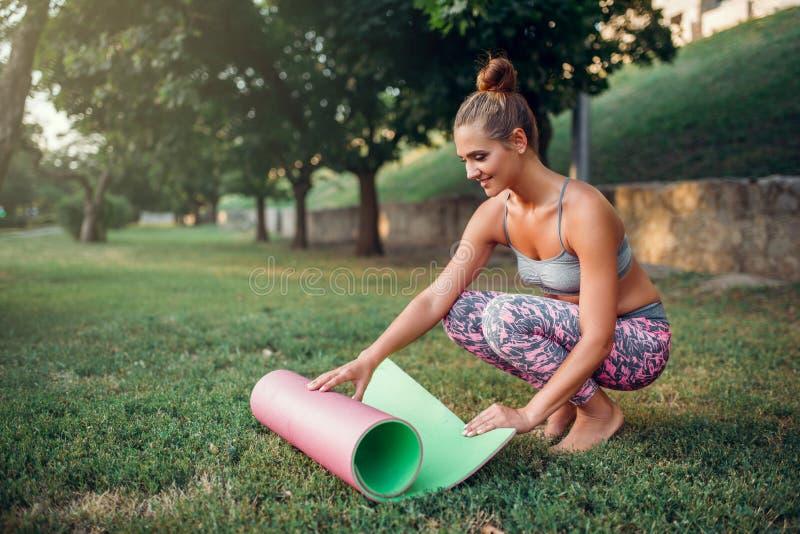 Циновка йоги завальцовки молодой женщины в парке стоковые фото