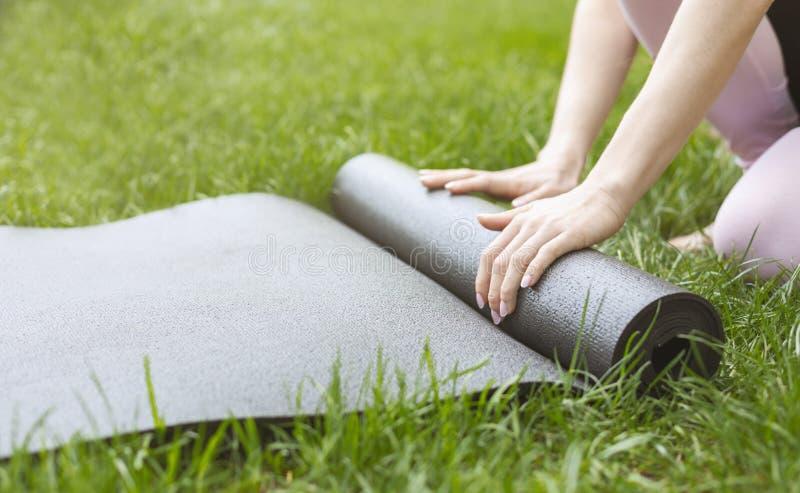 Циновка йоги молодой женщины свертывая перед или после практиковать outdoors стоковая фотография