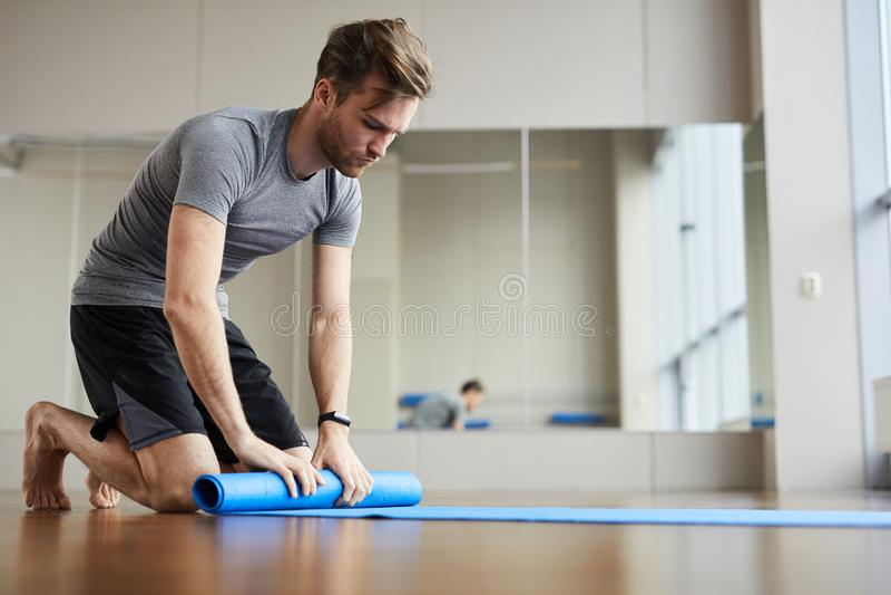 Циновка йоги упаковки молодого человека стоковая фотография rf