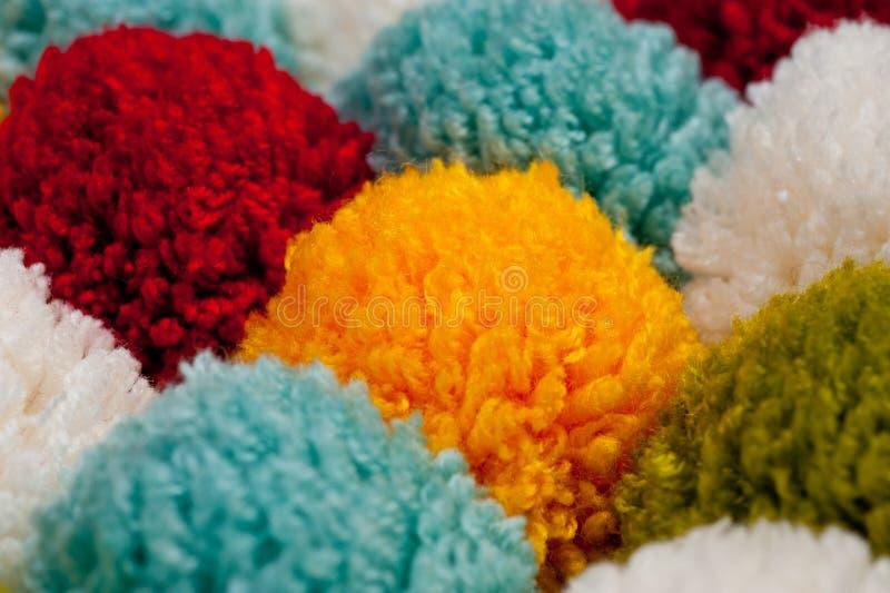 Циновка помпонов сделанных от пестротканой handmade пряжи стоковое фото rf