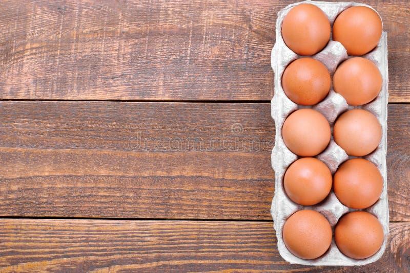 Цыпленок Брайна eggs в подносе для яичек на коричневой деревянной предпосылке стоковое фото rf