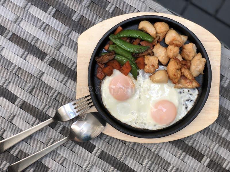 Цыпленок зажаренный с яичницей и овощем на горячем лотке и деревянное блюдо диеты плиты для рекламировать меню на ресторане Еда в стоковое изображение rf