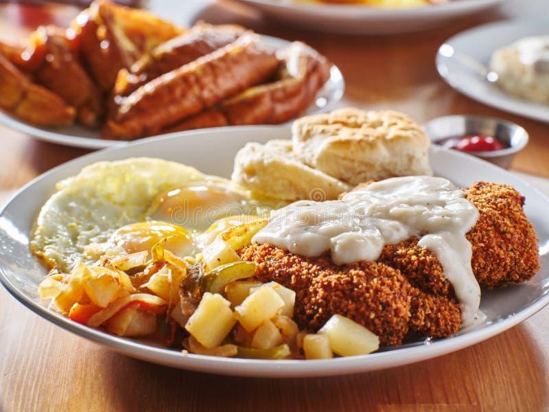 Цыпленок зажарил стейк предусматриванный в подливке с солнечной стороной вверх по яйцам и еде завтрака стоковые изображения