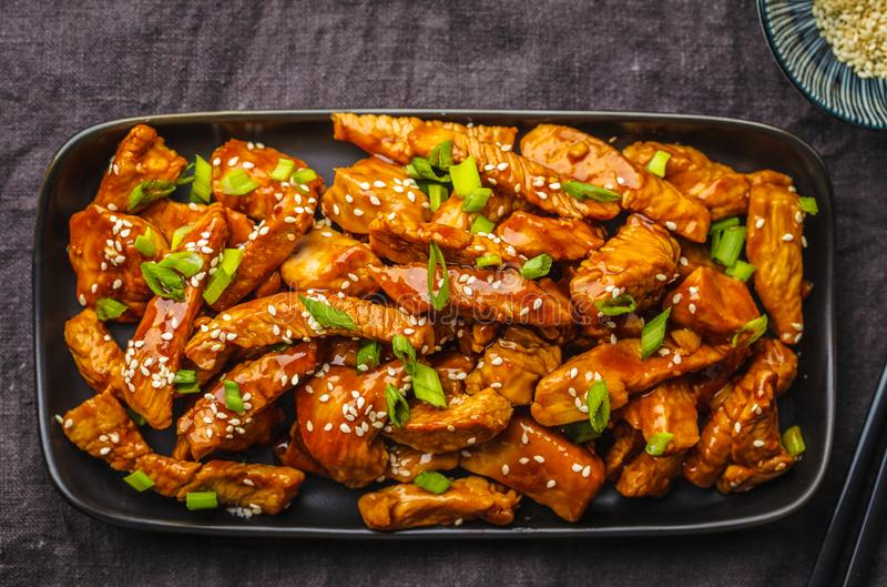 Цыпленок Teriyaki с сезамом, зеленым луком в черной плите, темной предпосылке стоковая фотография rf