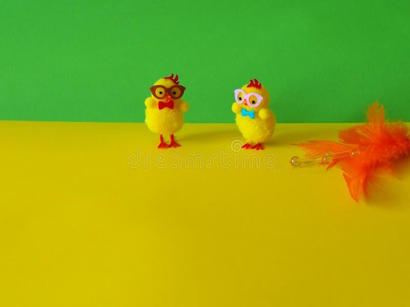 2 цыплят пасхи с оранжевым украшением на желтой и зеленой предпосылке стоковая фотография rf