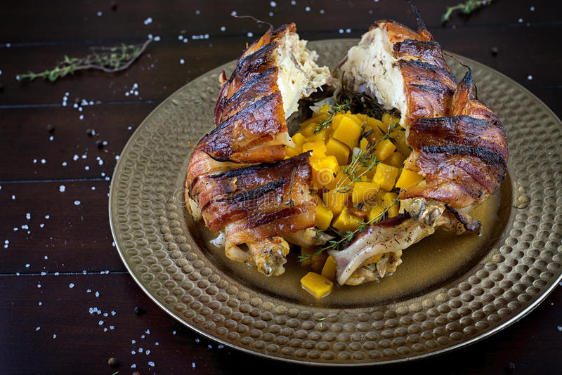 Цыпленк цыпленок обернутый беконом зажаренный в духовке заполненный с сквошом butternut стоковое фото