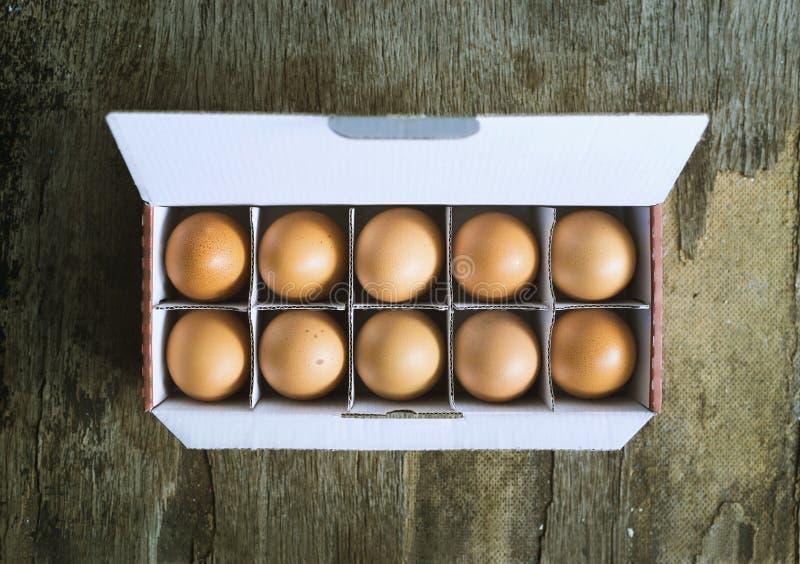Цыпленок Брайна eggs в коробке на деревянной предпосылке стоковая фотография