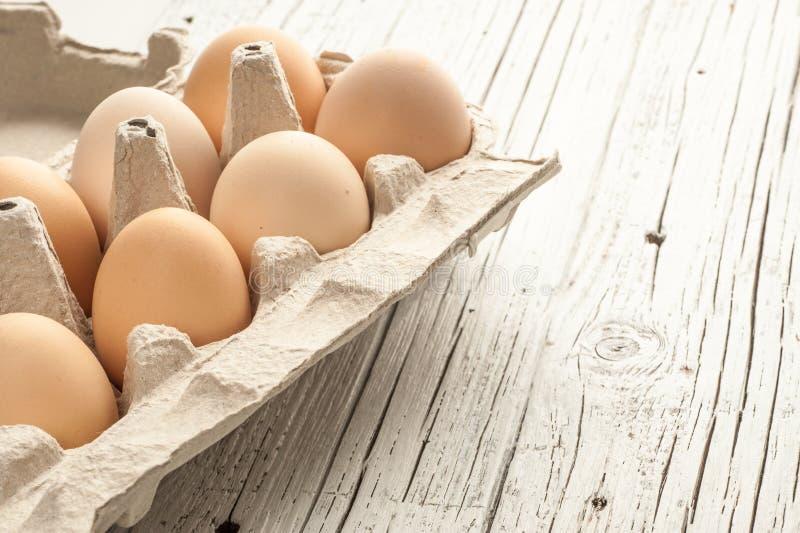 Цыпленок eggs в картонной коробке на белой деревянной предпосылке стоковая фотография rf