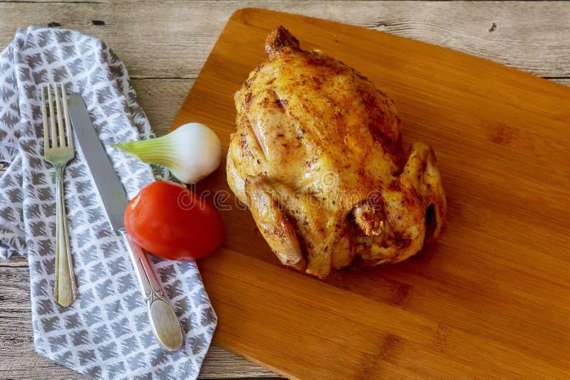 цыпленок rotisserie на деревянном подносе сервировки с стоковые фото