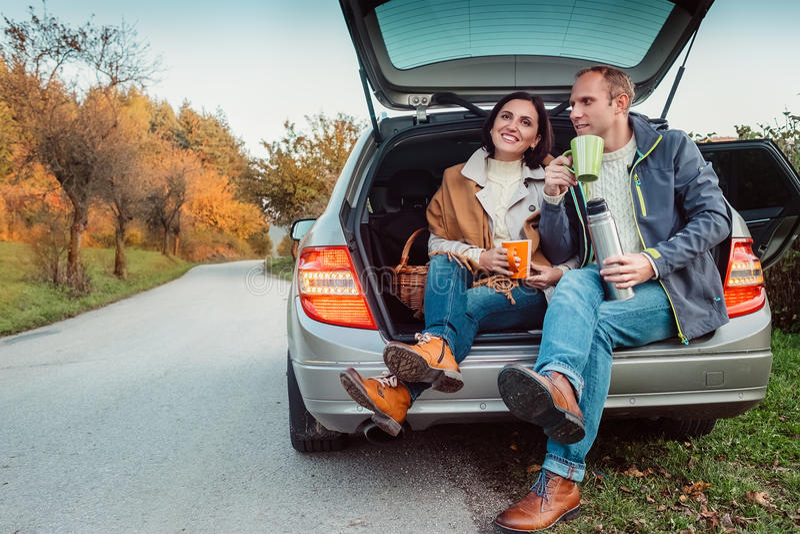 Чаепитие в багажнике автомобиля - любящая пара выпивает горячий чай от склянки thermos сидя в багажнике автомобиля стоковая фотография rf