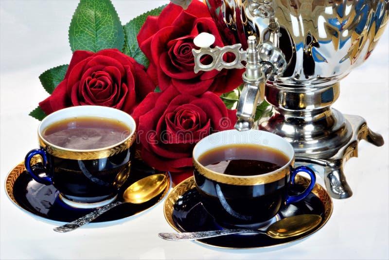 Чаепитие - самовар, чашки и розы сада ферзя цветков Самовар творческий для чая, русских традиций, символа колодца стоковая фотография rf