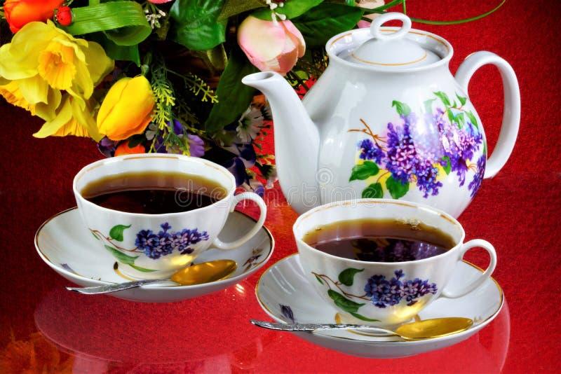 Чаепитие - чай в чашках, чайник, цветки сада на летний день Ежедневный чай очень вкусное, популярный, здоровый, поддерживающ напи стоковые изображения rf