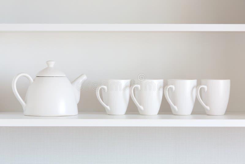 Чайник и чашки на полке стоковое изображение rf