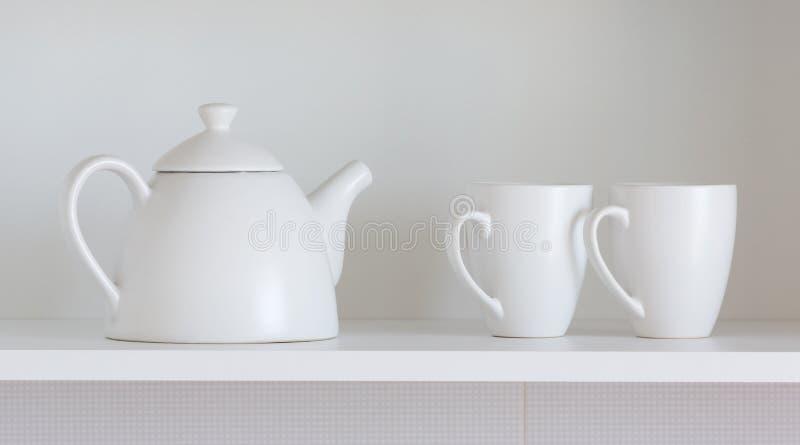 Чайник и чашки на полке стоковое фото rf