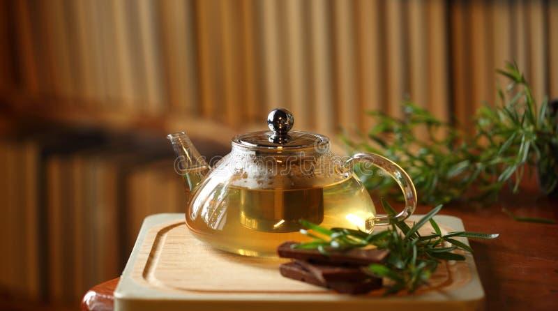 Чайник с чаем травы на деревянной разделочной доске с розмариновым маслом и шоколадом близко, книги на предпосылке, интерьере дом стоковая фотография rf