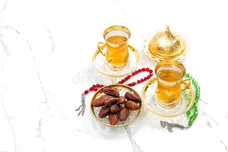 Чайные чашки изображены с розовыми бусиками на белом фоне Рамадан карим стоковые фото