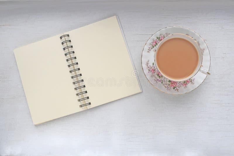 Чай в винтажных чашке и поддоннике, и тетради с пустыми страницами стоковое фото rf