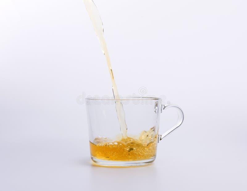 Чай гибискуса лить в чашке изолированной на белой предпосылке стоковое фото rf