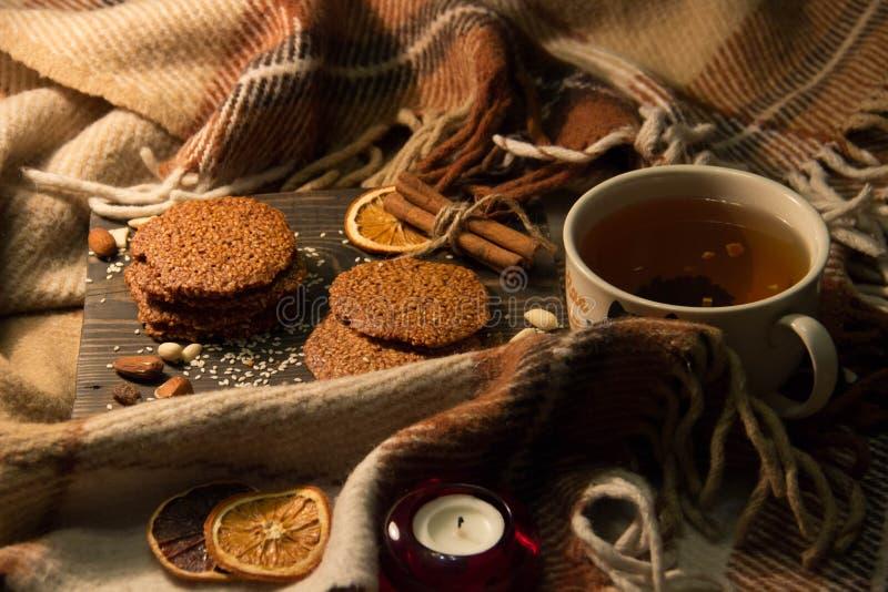 Чай, домодельные печенья с семенами сезама, высушенные плодоовощи и ручки циннамона стоковое фото rf