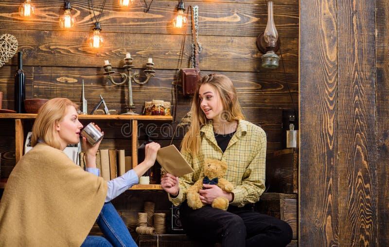 Чай женщины выпивая пока беседующ с ее дочерью Мама показывая альбом старой книги или семьи к девочка-подростку, традициям стоковое фото