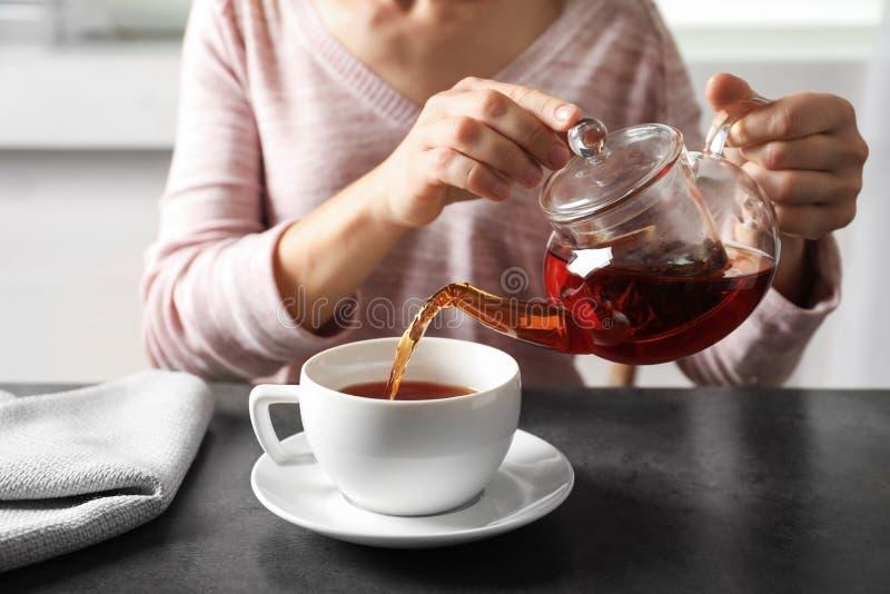 Чай женщины лить в чашку фарфора стоковое фото