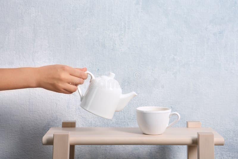 Чай женщины лить от бака в чашку на таблице против стены цвета стоковая фотография rf