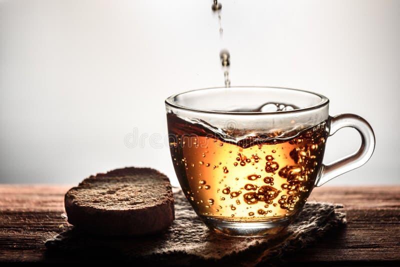 чай лить в стеклянную прозрачную чашку с пузырями и печеньем на деревянном столе стоковые изображения