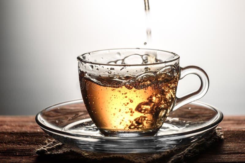 чай лить в стеклянную прозрачную чашку с пузырями на деревянном столе стоковые фото