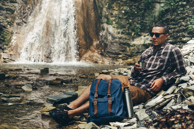 Чай или кофе питья человека Backpacker от Thermos на концепции перемещения назначения предпосылки водопада отдыхая располагаясь л стоковые изображения