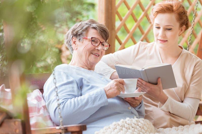 Чай и медсестра счастливой пожилой женщины выпивая читая ее книга внутри стоковая фотография