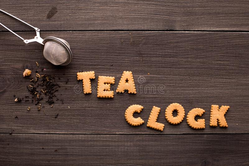 Чай и надпись печенья на деревянной предпосылке стоковая фотография