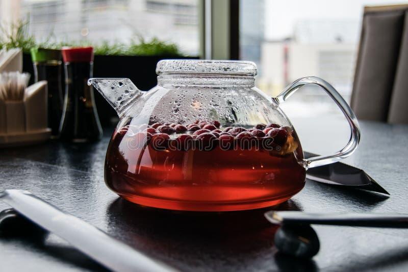 Чай клюквы в стеклянном чайнике стоковая фотография