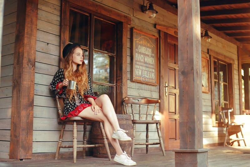 Чай/кофе девушки выпивая в Диких Западах, в западном доме Девушка в шляпе с длинными cerly волосами Красивая милая улыбка девушки стоковая фотография rf