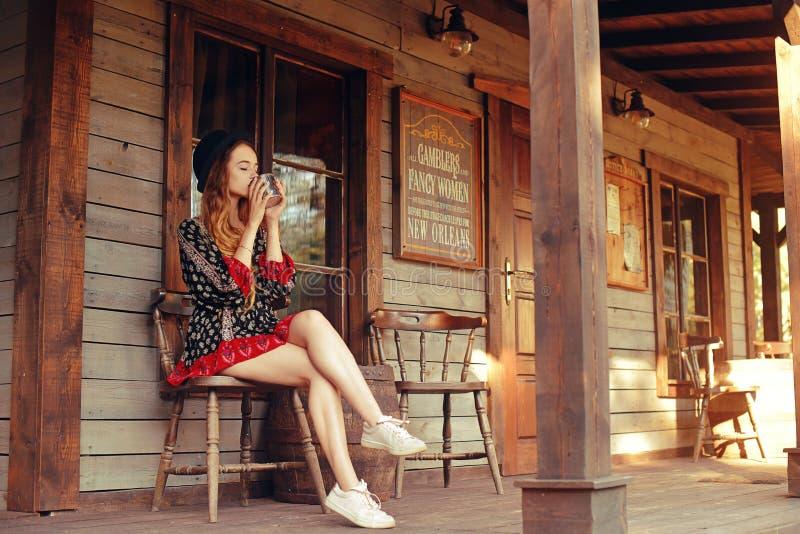 Чай/кофе девушки выпивая в Диких Западах, в западном доме Девушка в шляпе с длинными cerly волосами Красивая милая улыбка девушки стоковые фото