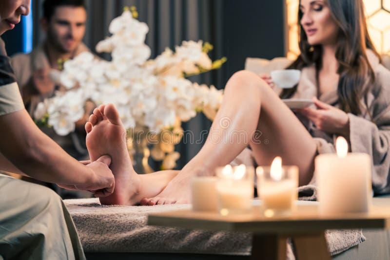 Чай красивой женщины выпивая во время терапевтического массажа ноги стоковые изображения rf