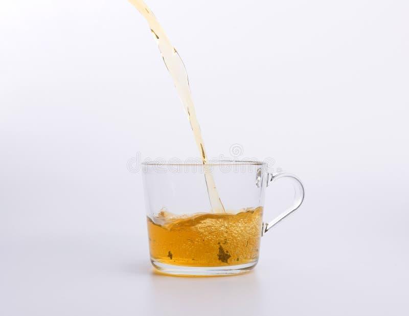 Чай лить в стеклянную изолированную чашку стоковое изображение rf