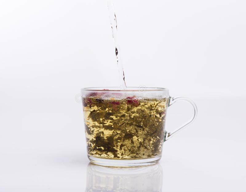 Чай лить в стеклянную чашку изолированную на белизне стоковые фото