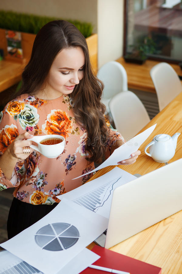 Чай молодой женщины выпивая, читая газеты стоковая фотография