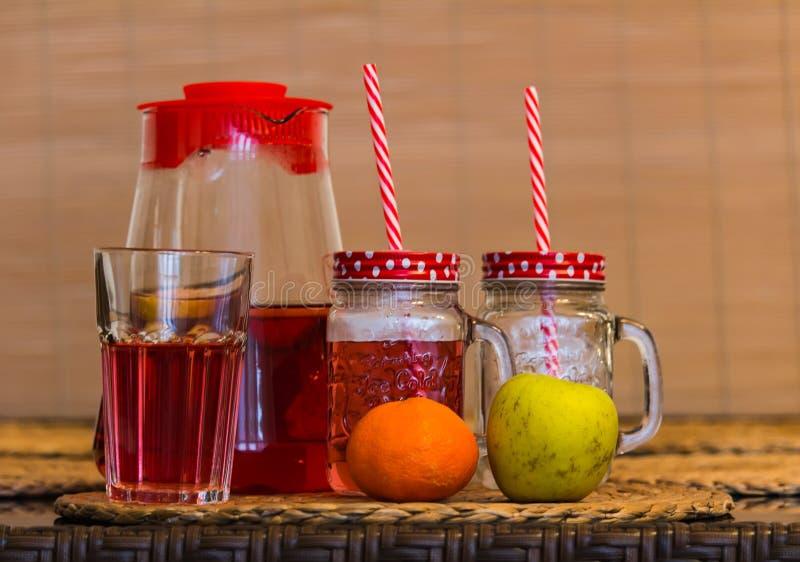 Чай плода в стекле с выпивая соломой, апельсином и яблоком на столе стоковое фото rf