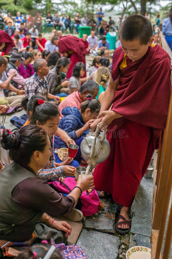 Чай подачи буддийского монаха тибетский к операторам на приеме во время его святости 14 преподавательства Далай-ламы Tenzin Gyats стоковая фотография rf