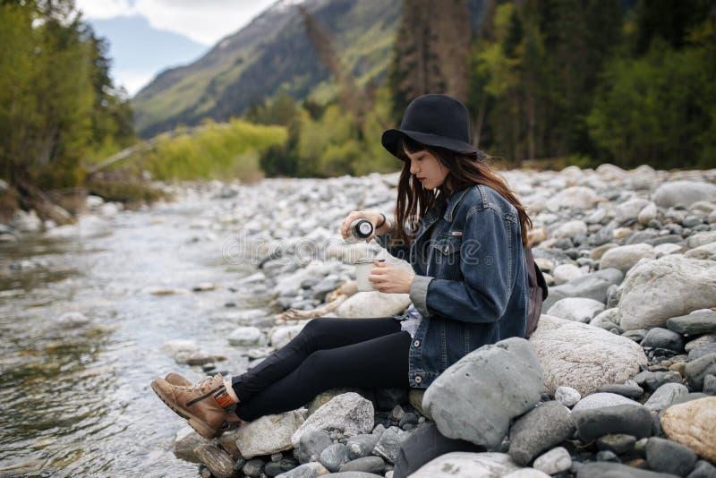 Чай рюкзака девушки нося выпивая от thermos и смотреть озеро стоковая фотография