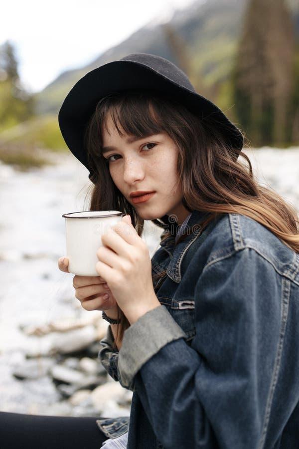 Чай рюкзака девушки нося выпивая от thermos и смотреть озеро стоковое фото rf