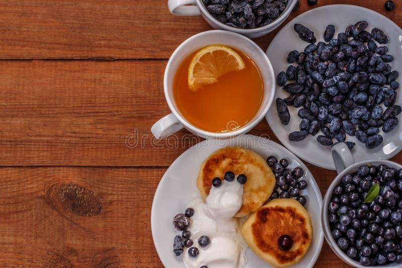 Чай с лимоном, тортами с сметаной, изюминками, каприфолием и голубиками на коричневой деревянной предпосылке стоковые фотографии rf
