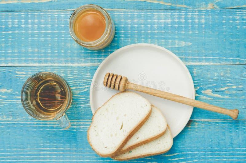 чай с медом и отрезанные белые куски печениь на деревянной голубой предпосылке таблицы r стоковая фотография rf