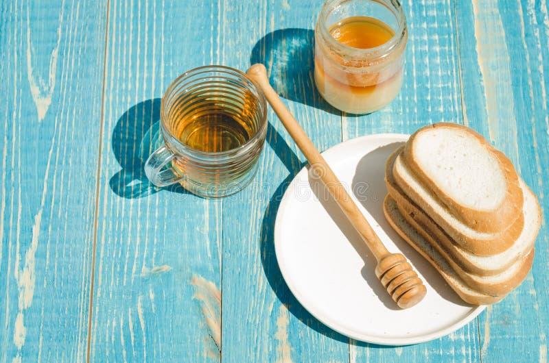 чай с медом и отрезанные белые куски печениь на деревянной голубой предпосылке таблицы r стоковая фотография