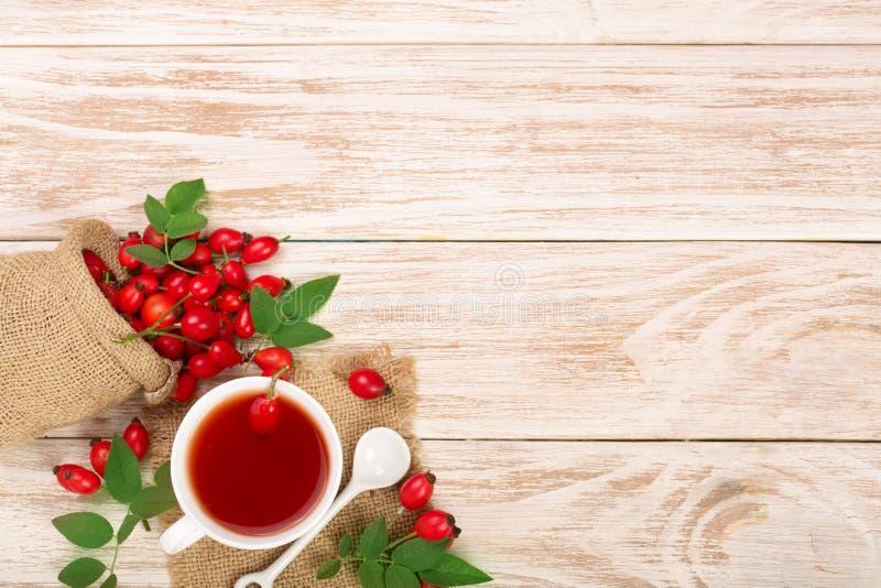 Чай с плодами шиповника и медом на белой деревянной предпосылке с космосом экземпляра для вашего текста Взгляд сверху стоковые фото